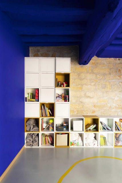 Vue de l'espace dortoir du projet de l'Ecole Montessori Square Paris 18 avec un focus sur le mur en pierres apparentes associé au fameux Bleu Klein très puissant de Ressource Peinture sur le plafond et dynamisé par l'ajout de rangements jaune ocre.