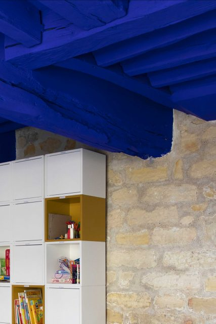 Détail de l'espace dortoir du projet de l'Ecole Montessori Square Paris 18 avec un focus sur le mur en pierres apparentes associé au fameux Bleu Klein très puissant de Ressource Peinture sur le plafond et les poutres structurelles.