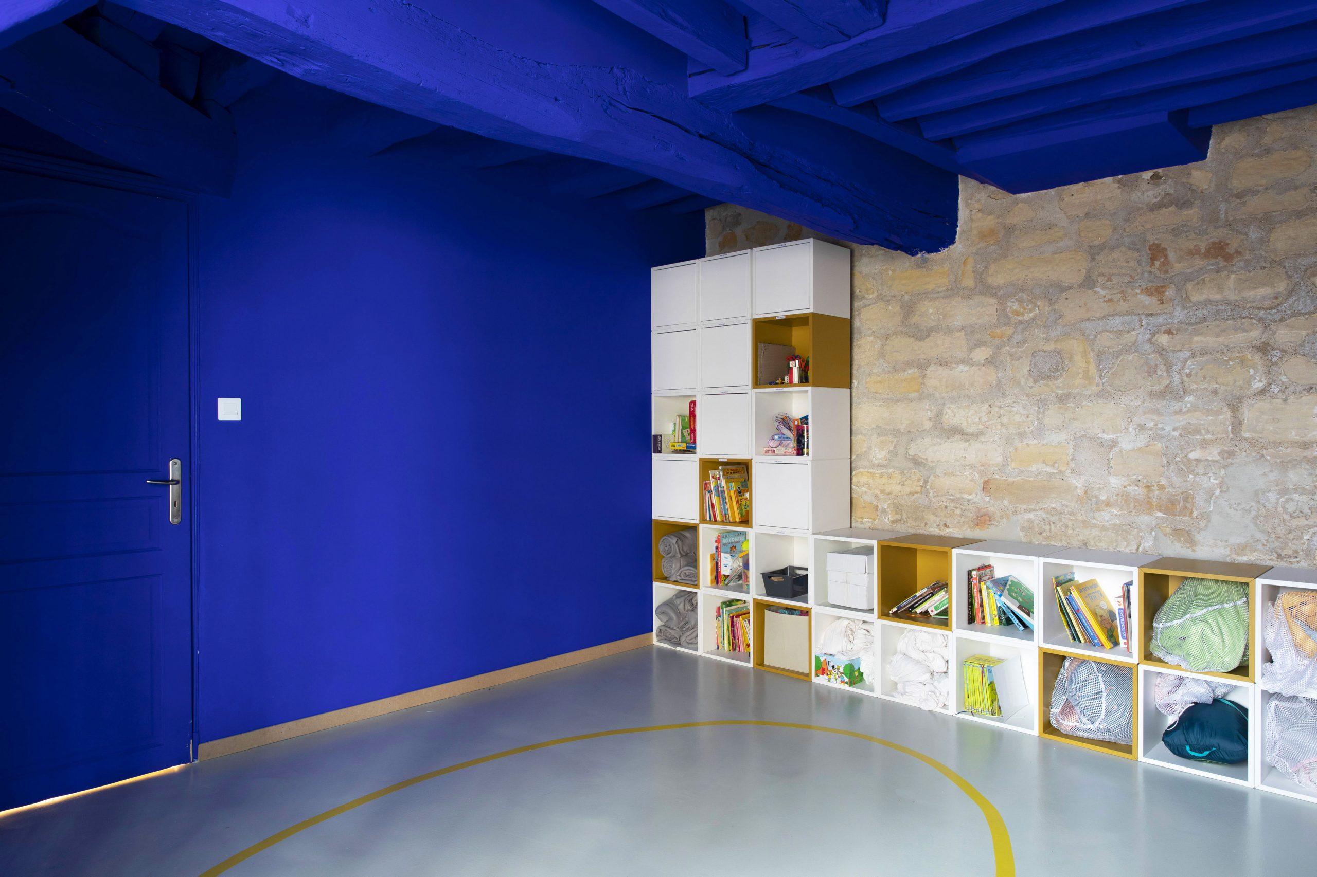 Vue de l'espace dortoir du projet de l'Ecole Montessori Square Paris 18 avec la conservation de son mur en pierres apparentes dynamisé par une mise en peinture des murs adjacents et du plafond avec le fameux bleu Klein de Ressource Peinture.