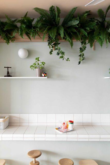 Vue sur l'espace d'expérimentation de l'Ecole Montessori Square Paris 18 conçu comme une paillasse de labo avec son plan de travail carrelé blanc, le tout adouci par un doux vert-de-gris et la présence de végétation luxuriante en partie haute.