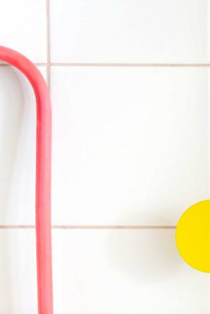 Détail sur la mise en valeur colorée et graphique du système de plomberie des points d'eau pour enfants en écho au mur orange fluo de la cage d'escalier attenante pour le projet de l'Ecole Montessori Square Paris 18.