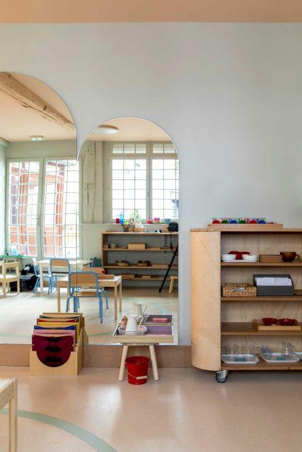 Vue de l'espace manipulation et motricité du projet de l'Ecole Montessori Square Paris 18 avec un grand miroir sur mesure à tête cintré pour réfléchir la lumière de la cour attenante et ouvrir l'espace étroit ainsi que son meuble mobile de rangement permettant d'organiser l'espace et créer dans cet espace ouvert divers zone d'apprentissage..