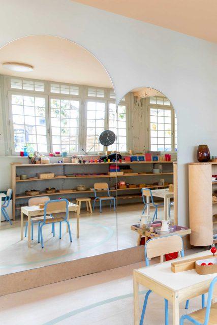 Vue de l'espace manipulation et motricité du projet de l'Ecole Montessori Square Paris 18 avec ses teintes vert-de-gris et rose pâle pour un écrin doux aux divers plateaux colorés de manipulation / apprentissage en autonomie ainsi que son très beau miroir sur mesure à tête cintré.