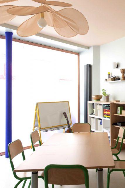 Vue sur l'espace de travail donnant sur la rue de l'Ecole Montessori Square Paris 18, baigné de lumière et fort de son parti pris coloré rose et vert-de-gis, une jolie suspension en tissu Pale Georges détourne les codes de l'école et initie à l'art de la légèreté.