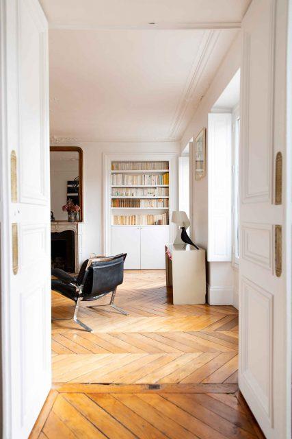Vue globale du salon et sa bibliothèque sur mesure accueillant discrètement la télévision sur bras télescopique sur le projet de la rue des Martyrs Paris 9ème.