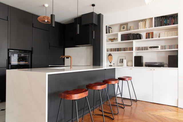 Vue globale de la cuisine noire et blanche sur laquelle se greffe une bibliothèque sur mesure pour le projet de la rue des Martyrs Paris 9ème.