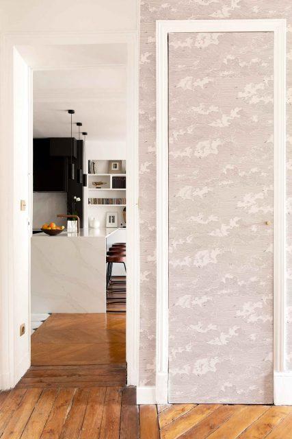 Vue depuis la salle à manger vers la cuisine ouverte nouvellement créee, volume noir mat, marbre Calacatta blanc et papier peint délicat noir & blanc au premier plan du projet de la rue des Martyrs, Paris 9ème.