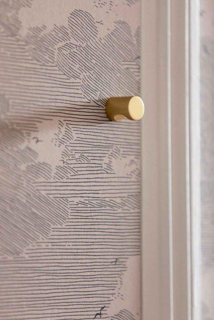 Détail des rangements crées sur les niches existantes recouvertes de papier peint noir et blanc et bouton de meuble en laiton sur le projet de la rue des Martyrs Paris 9ème..