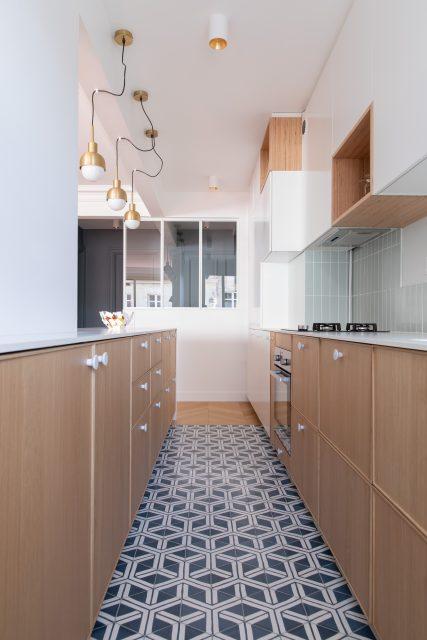 Vue de la cuisine tout en longueur du projet Paris 16 avec ses teintes douces de façades chêne clair, crédence bleu clair dynamisé par un sol graphique de carreaux de ciment bleu et blanc de Popham Design et la vue ouverte sur l'entrée bleue grise grâce à sa verrière blanche.
