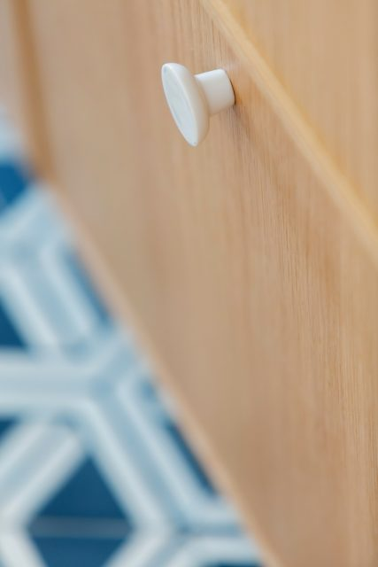 Détail de la cuisine du projet Paris 16 avec ses façades chêne clair, ses poignées en porcelaine blanches contrastant avec le sol graphique de carreaux de ciment bleu et blanc Popham Design.