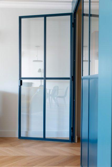 Détail de la porte vitrée de la verrière sur mesure bleue délimitant le bureau et son reflet de l'espace de vie attenant du projet Paris 16.