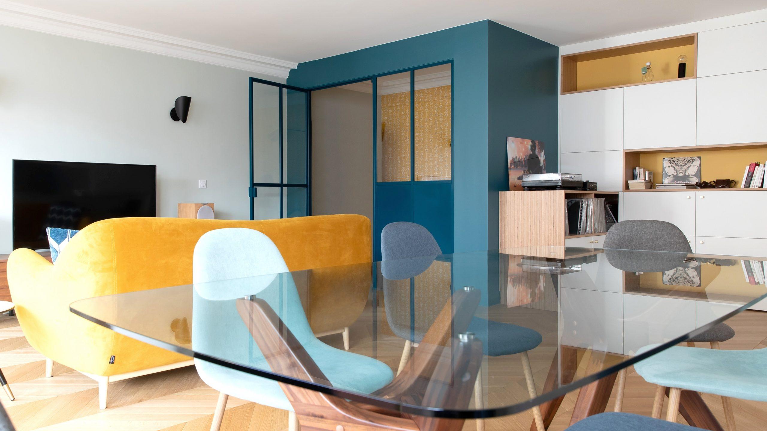 Vue de l'ensemble de l'espace salon / salle à manger du projet Paris 16 avec l'alcôve bureau vitrée bleue et son papier peint jaune en résonance avec le canapé jaune.