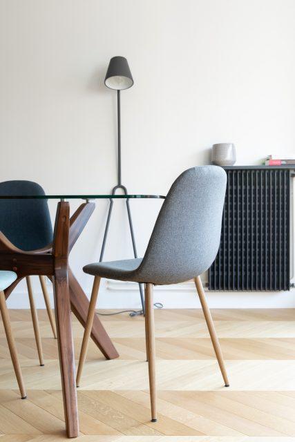 Vue de l'espace salle à manger minimaliste et contrastée avec sa table verre et noyer AMPM, ses chaises en tissu grises ainsi que son radiateur anthracite se détachant sur le mur blanc, Projet Paris 16