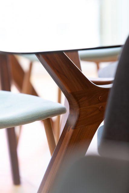 Détail sur la table en verre et piétement en noyer AMPM et les chaises tissées vert de gris de la salle à manger du projet Paris 16.