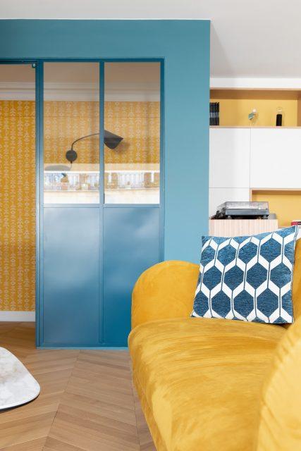 Détail sur la verrière sur mesure bleue délimitant l'espace bureau intégré au vaste salon salle à manger du projet Paris 16. Résonance ensoleillée du jaune moutarde du canapé et du papier peint.