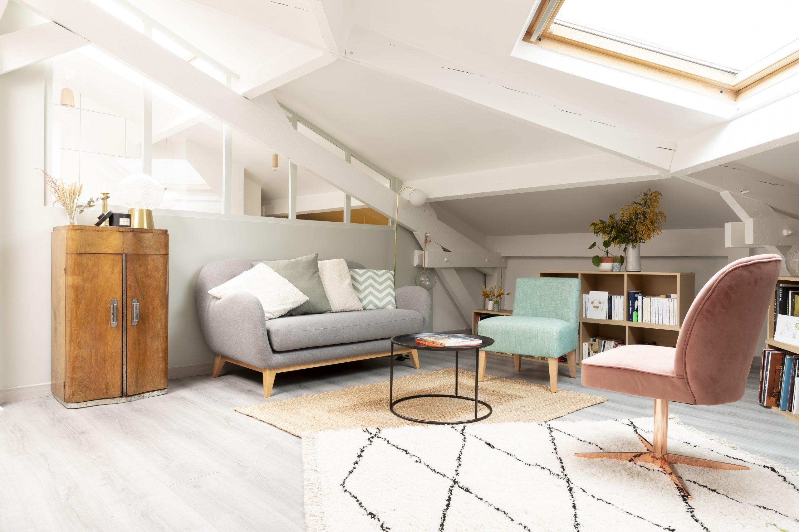 Vue sur le salon sous combles, ses teintes douces vert de gris et l'espace alcôve vitré du bureau pour le projet Ribera Paris 16 sous les toits de Paris.