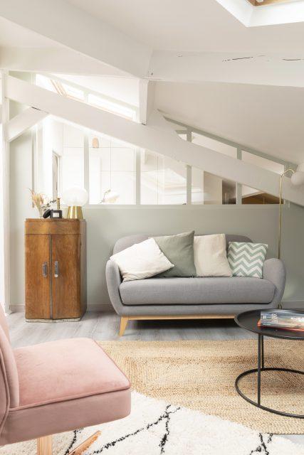 Vue sur le salon du projet Ribera Paris 16, ses teintes douces vert de gris, l'espace alcôve vitrée du bureau et la charpente des combles rendant ce lieu insolite.