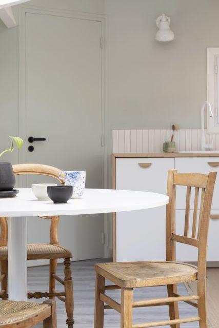 Vue sur l'espace salle à manger et sa jolie table ronde réchauffée de chaises chinées en bois avec en arrière plan la cuisine blanche, bois et vert-de-gris du projet Ribera Paris 16.