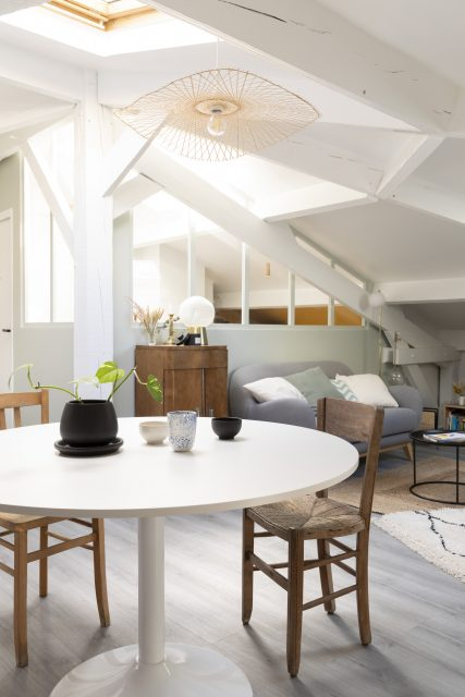 Vue sur l'espace salle à manger et sa jolie table ronde réchauffée de chaises chinées en bois avec en arrière plan l'alcôve bureau et sa verrière en bois peinte se nichant contre la structure insolite des combles du projet Ribera Paris 16.