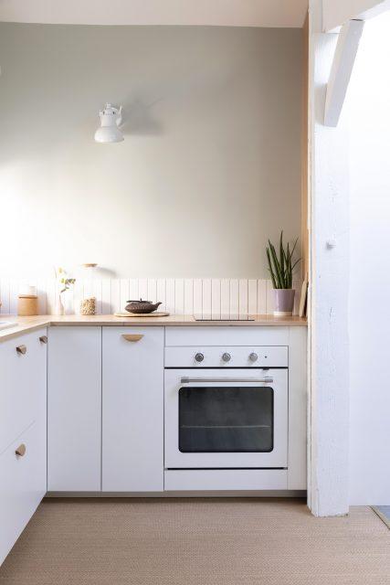 Vue sur la cuisine aux tonalités douces vert de gris, blanche et bois avec son sol tressé délimitant l'espace cuisine au sol, projet sous les toits Ribera Paris 16 .