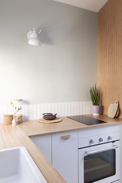 Vue sur la cuisine aux tonalités douces vert de gris, blanche et son plan de travail en bois créant une alcôve cuisine de par sa continuité en joue de finition, Projet sous les toits Ribera Paris 16 .
