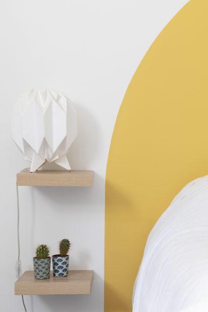 Détail de la tête de lit graphique en demi cercle peint jaune soleil de cette petite chambre sous les toits de Paris du projet Ribera Paris 16.