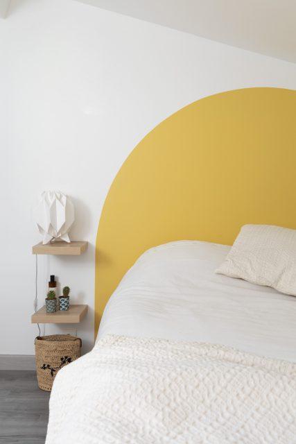 Vue sur la tête de lit graphique en demi cercle peint jaune soleil de cette petite chambre sous les toits de Paris du projet Ribera Paris 16.
