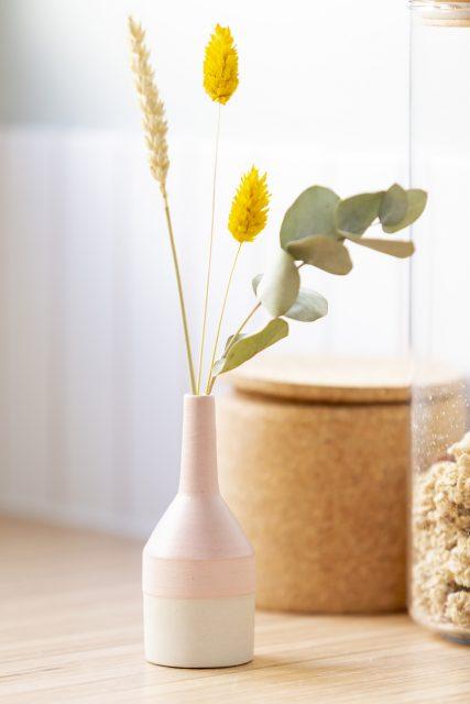 Détail de la cuisine avec ses touches de vases délicat et fleurs séchées en écho au papier peint fleuri de la salle de bain du projet sous les toits de Paris du projet Ribera Paris 16